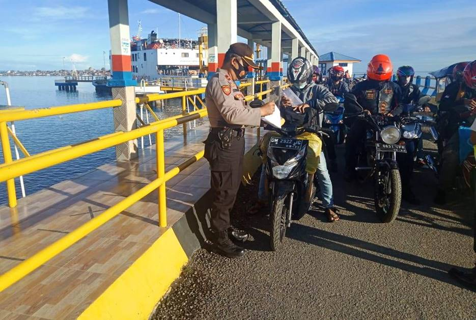 Anggota Polsek Pagimana memeriksa penumpang kapal fery dari Gorontalo yang tiba di pelabuhan penyebrangan Pagimana, Rabu pagi (27/1). [Foto: Istimewa]